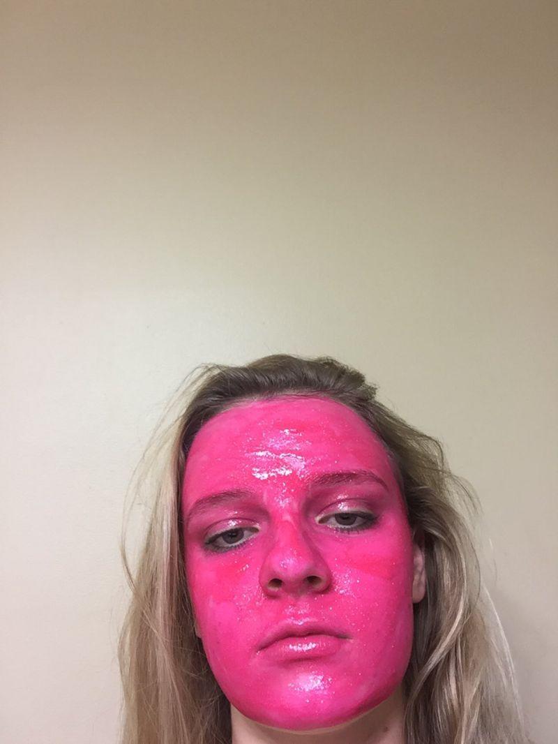 Девушка покрасила лицо розовой краской. Зачем?